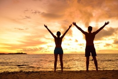Couple on beach with arms outstretched